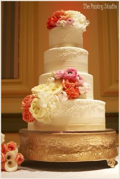 A Formal Piped & Scrolled Wedding Cake with Fresh Florals