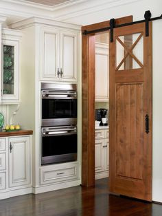 Avoid the dreaded swing door; a barn door separates kitchen and pantry--BSB Designs