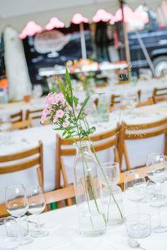 Romantische bloemen in eenvoudige vaas als decoratie voor de dinertafel tijdens een tuinbruiloft.