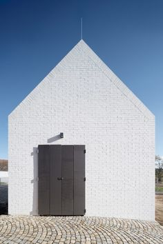 The gabled design and black roof tiling are intended to blend in with the local architectural vernacular, but the architects chose to use the white-painted brick walls to mark its significance.