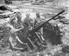 Curious minded Marines take the seats and positions of former Jap gunners, around a 25mm anti-aircraft, twin mount gum emplaced in the west airfield area on Peleliu.