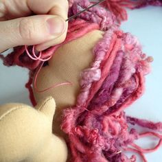 Now that we have the face embroidered, it is time to do the doll's hair!  This is a lot easier than you are envisioning it and actually a lot of fun! To start you will need yarn for the hair, a 2.5 or 3″ doll makers needle, and embroidery floss matching your dolls hair …