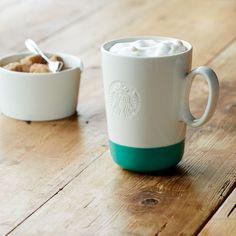 A hi-shine ceramic coffee mug with a turquoise base and angled handle.