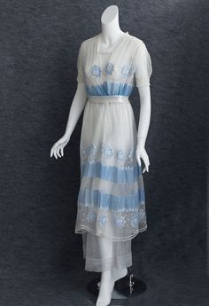 1912 B. Altman embroidered tea dress in a crisp blue-and-white palette. This dress is made from cotton batiste and cotton tulle and is embellished with blue embroidered floral appliqués.