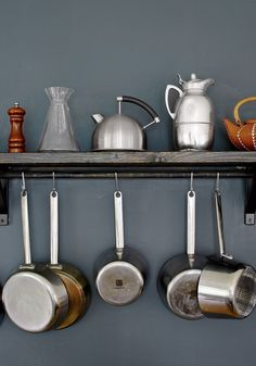 To save space in the small kitchen, the couple hangs their pots and pans on a hook underneath a long open shelf.