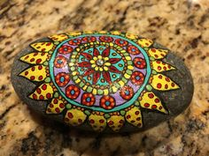 Acrylic paint and river rock..Fantastic design and colors make up this beautiful flower mandala!!