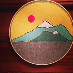 Embroidery Hoop Art,  Wall Art, Felt, Mountains, Mountain Range, Yellow, blue, green, and pink sun with grey linen