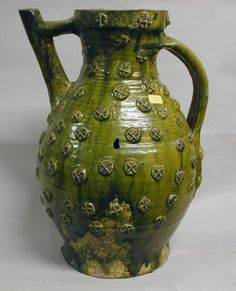 1150 - 1250. Jug   York Museums Trust. Jug with copper green glaze over all exterior except near basal edge. Decorated throughout with small circular bosses with equal-armed cross in relief. Tubular spout attached to neck with bridge.
