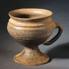 #Cup with Handle 	 #Korea; Three Kingdoms period, Kaya kingdom (42-562 B.C.E), early 6th century  This petite cup consists of a rounded body atop a skirt-like foot and a prominent handle. Its main body is decorated with incised crisscrossing lines, and its foot punctuated by small holes. Pieces similar to this cup have been discovered from earthen mound tombs in #Pusan on the southeastern coast of Korea. #museum #history #earthenware