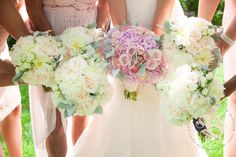 Lush Garden Wedding by Bride & Blossom:  Sweet, bohemian, vintage bouquets in a soft color palette of pale pink, white and green.  Bridal bouquet: pink peonies, blush roses, pink ranunculus, and dusty miller.  Bridesmaids: white dahlias, cream roses, cream spray roses, and dusty miller. Photo: Emma McDonald Weddings