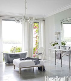 """""""I love a glamorous bathroom,"""" Watson says. He turned the master bath into a spa-like oasis with floor-to-ceiling windows, a Waterworks cast-iron tub, a custom vanity with crystal bars, also by Waterworks, and a crystal chandelier from John Salibello. Walls are Silver Satin in Aura by Benjamin Moore."""