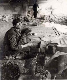 Nordhausen, Germany, April 1945, A survivor sitting beside a pot of potatoes.