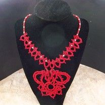 For the carefree, this free spirited medallion necklace is for you. Perfect for casual social events, it will attract attention with its unique design and its red and silver beaded accents.  This lacy piece of jewelry is needle tatted from #10 cotton thread. It is 17 inches long and has a lobst...