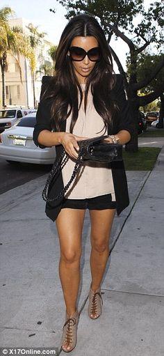 Stylish: Kim teamed her shorts with a blazer and Chanel handbag