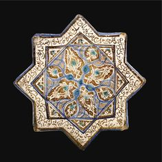 An Exceptionally Fine Kashan Lustre Star Tile, Persia, Dated A.H. 680/A.D. 1281-1282 of stellar form, decorated in dark brown lustre, cobalt blue and turquoise with a central cruciform design radiating lotus palmettes reserved on a scroll ground alternating with lobed cartouches filled with scale and dot patterning bordered by a calligraphic band, with modern stand