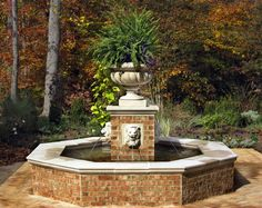 Cast concrete lion heads spit streams of water into an octagonal pool. Pool walls and a central pillar are veneered in brick to match the surrounding patio. Design and installation by Merrifield Garden Center.