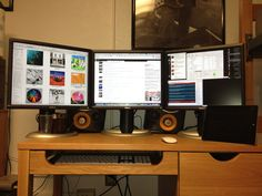 Hackintosh setup on a little desk. Interesting look... maybe too many monitors?