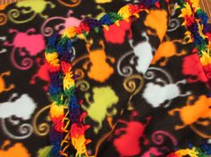 This is a wonderful soft and supple fleece blanket in brilliantly colored monkies. The edge is a soft variegated yarn of bright colors crocheted into