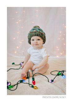 One year old boy with Christmas lights and winter hat photographed by Brenda Landrum Photographer of Fort Collins Colorado.