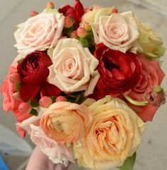 Garden bridesmaids bouquet - Inspired by the sunset. Coral, red, yellow, peach roses.  coral hypericum berries.  Peach, orange, yellow ranunculus.