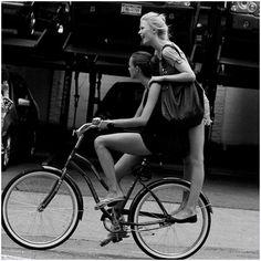 black & white. Two girls on a bike.