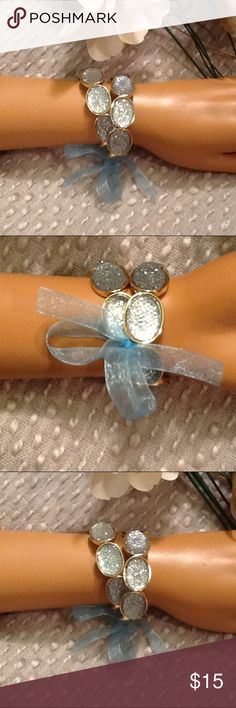Double Strand Bracelet NWOT Baby Blue Sparkle Gems Gorgeous double strand stretch bracelet, NWOT, beautiful baby blue sparkle oval stones, gold platted, with a pretty baby blue ribbon attached, unsure of the brand. Even though this is a stretch bracelet, this seems to fit small wrists better, 6 to 7 inches, because the fit is tighter. Very elegant, perfect to wear for any occasion!  Bundle to save 15% off any purchase of 2 or more items from my closet! Jewelry Bracelets