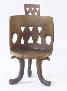 AN ETHIOPIAN WOODEN CHAIR, on three curved legs, each joined by a vertical strut to the border of the circular seat, the rectangular backres...