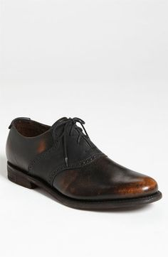 Handsomely burnished leather adds vintage appeal to a traditional two-tone saddle shoe with durable Goodyear® welt construction.  Lace-up style.  Leather and canvas upper/leather lining and sole.  By J.D. Fisk; imported