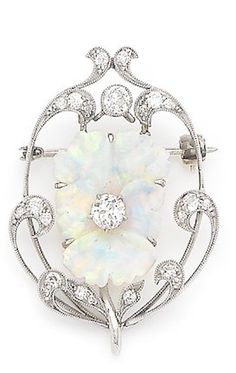 An opal and diamond pansy brooch, circa 1905. The opal finely carved to depict a pansy in bloom, centrally-set with an old brilliant-cut diamond, to a scrolling openwork surround millegrain-set with similarly-cut diamonds, diamonds approx. 0.90ct total, numbered, length 4.0cm.