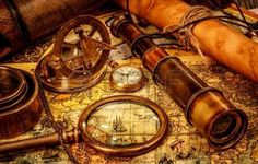 Vintage magnifying glass compass telescope and a pocket watch lying on an old map  Stock Photo: