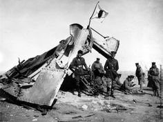 1914: British and Japanese officers stand by a Japanese flag flying over a wrecked German gun after the siege of Tsingtao