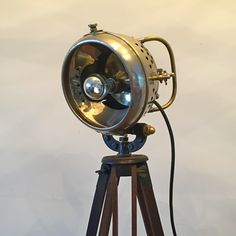 Vintage Tripod Lamp  Build from a old-timer searchlight dated 1910 and a very old camera tripod dated 1920 Details searchlight: Phares Auteroche Model 295 Details tripod: Hardwood restored vintage camera tripod dated 1920 Completed with new wiring, lamp socket and lightbulb