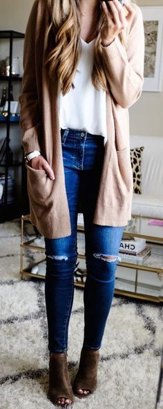 Cute winter outfit. White T-shirt with light brown cardigan and a pair of blue jeans. Brown open-toed booties.