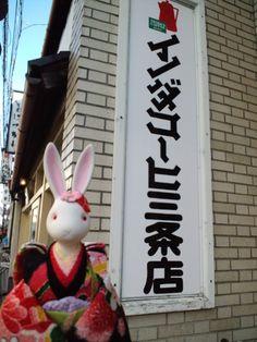 【イノダコーヒ三条店】   1940年6月に猪田七郎が海外産コーヒーの卸売を始め、1947年8月にコーヒーショップを開いたのが創業です。この時、客が会話に夢中になってコーヒーが冷め、砂糖とミルクがうまく混ざらなかった事がきっかけとなり、初めから砂糖とミルクを入れた状態でのコーヒーの提供が始められました。三条店には、特徴的な円形カウンターがあり、目の前でコーヒーを漉す様子が見えることから、多くの常連がこの円形カウンターに座ります。店名は「イノダコーヒー」ではなく「イノダコーヒ」です。