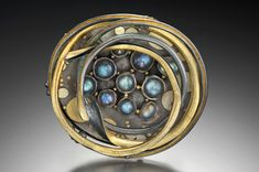 Brooch   C.H. Mackellar.  Labradorite set within a swirl of oxidised sterling and 18kt gold with fused 18kt and 22kt details.