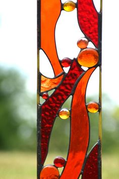 Stained glass garden art that brings on the heat. Red and orange stained glass add lots of color to your garden decor. Drought tolerant...never needs watering. It Sizzles! As with all my garden sculptures, this was designed so that the wind will pass through with no bother. Dimensions: 4 w x 32h, including 7 to plant. Gift idea: Gift for gardener, birthday, gift for him Construction: Textured stained glass and glass nuggets carefully soldered to brass rods. Black patina applied. Ships wi...