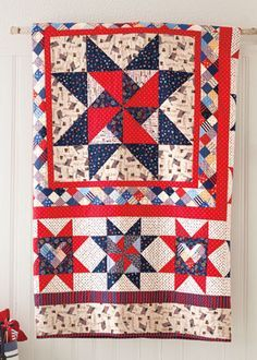 """""""One Nation"""" by Heidi Pridemore is from the July/August issue of Love of Quilting magazine. This patriotic red, white, and blue quilt pattern features hearts and pinwheels to fill the star quilt blocks that encircle the large center quilted medallion."""