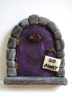Fairy Door for a curmugeonly fairy.  The sign and eyeball glow in the dark.