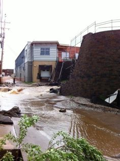The retaining wall below the Whole Foods parking lot washed out where Brewer Creek runs under it.
