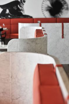 DETAIL | Banquette seating with stone curved back and soft cushions. High contrast white to red. #Banquette [ok]