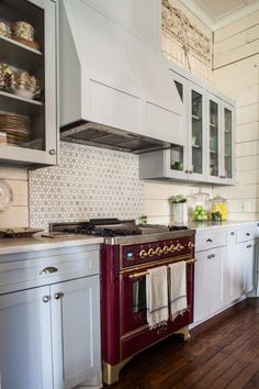 The eye is immediately drawn to the vibrant purple oven that pops against the gray cabinets and creamy walls in this country-style kitchen. A gray tile backsplash helps connect the lower cabinets to the upper cabinets and matching range hood. Dark hardwood flooring completes the look.