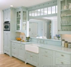 A pale blue Victorian kitchen with matching blue countertops, a white apron sink, glass cabinets, and a large pass through window