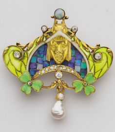 An Art Nouveau pendant-brooch, by Léopold Albert Marin Gautrait for Léon Gariod, French, circa 1900. Pendant brooch with a female head, composed of gold, enamel, diamond, opal and pearl.