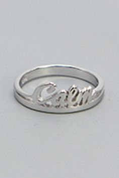 """Keep calm close at hand with this dainty ring, featuring the word """"calm"""" on its band. The ring's cursive font imbues this peaceful word with a human touch. Made of sterling silver and available in ring sizes 6-10. It Band, Band Rings, Peaceful Words, Cursive Fonts, Inspirational Jewelry, Dainty Ring, Ring Sizes, Jewelry Design, Silver Rings"""