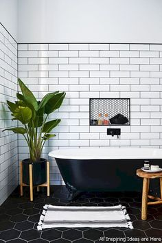 #black #tub and hexagon floor tile #tile, #warm wood accents and #house plant soften the palette