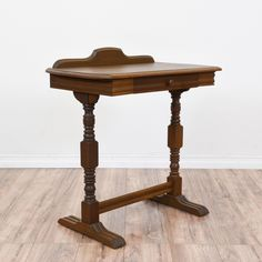 This rustic console table is featured in a solid wood with a glossy dark walnut finish. This small writing desk is in great condition with intricate carved spindle legs, a trestle base and 1 drawer. Perfect for an entryway or foyer! #rustic #tables #consoletable #sandiegovintage #vintagefurniture