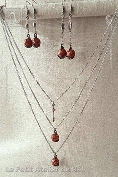 """[ Fait-Main ] avec du fil aluminium Marron Chocolat Mat, des chaînes, des anneaux et des crochets d'oreille en acier inox, des perles métalliques dites """"tibétaines"""". Le collier est réalisé avec trois chaînes en dégradé de tailles pour donner un effet cascade. Chaque pendentif cuivré scintillant est fait d'une perle de résine dont le mélange, préparé à la main avec soin, est composé de pigments et de micas. L'aspect souhaité : un rendu telle une nébuleuse profonde, dense, intense, cuivrée..."""