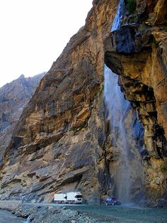 Waterfall washing all cars and trucks passing by a mountain road, Pamir Mountains, Tajikistan