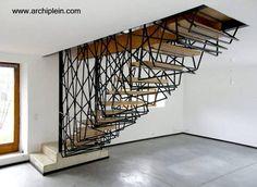 El soporte de los escalones de madera es una jaula de metal intrincada - Arquitectura www.archiplein.com