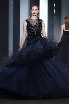 Midnight blue pleated tulle asymmetric ballgown with crystal, velvet and feather embellishment.